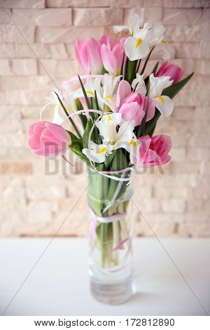 Vase with beautiful bouquet of flowers on table against brick wall background
