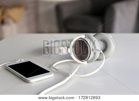 Headphones and cellphone on table and blurred background