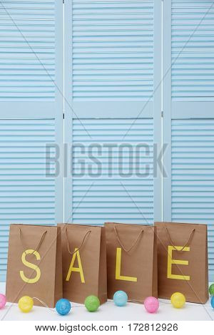 Word SALE on paper shopping bags against folding screen background