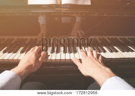 Male hands playing piano, closeup