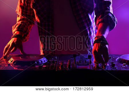 DJ mixing tracks on a mixer in a nightclub
