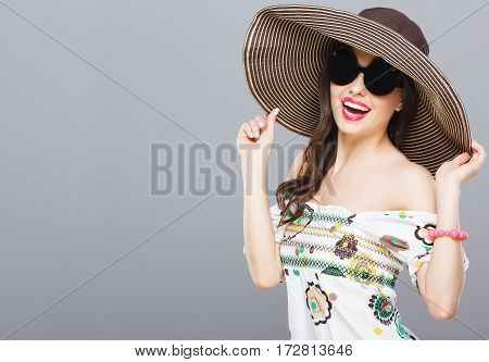 Beautiful girl in hat and black round sunglasses. Looking at camera, smiling. Holding hat with both hands. Summer outfit, floral dress. Waist up, studio, indoors