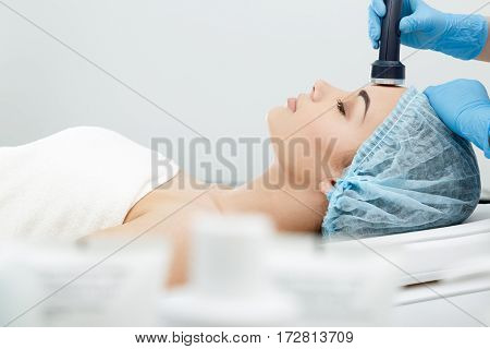 Hypersonic Phonophoresis. Model with closed eyes and hand's of doctor. Cosmetological clinic, procedure. Profile. Healthcare, clinic, cosmetology
