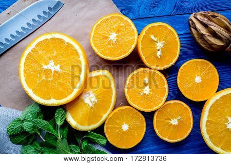 fresh orange juice squeezing on blue wooden kitchen table background top view