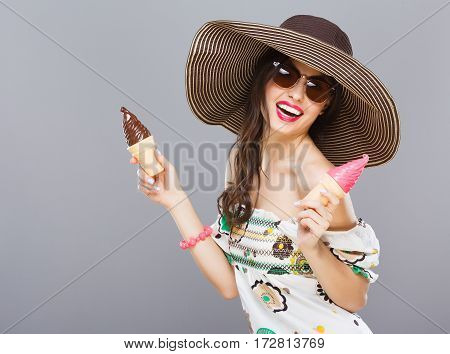 Beautiful girl in hat and sunglasses smiling widely. Holding two colorful ice-creams. Looking at camera, touching hair. Summer outfit. Waist up, studio, indoors