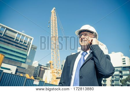 Senior engineer man in suit and safety helmet talking mobile phone.