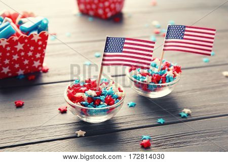 Sprinkles in glass bowls with USA flag on wooden background
