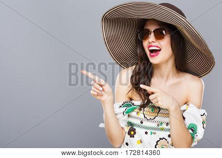 Cheerful beautiful girl in hat and sunglasses. Smiling widely, looking at camera and pointing aside. Summer outfit. Waist up, studio, indoors