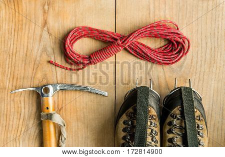 climbing equipment: rope, trekking shoes, ice tools, ice ax, crampons on wooden background, top view