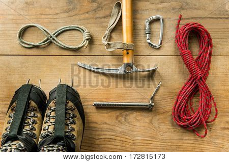 climbing equipment: rope, trekking shoes, ice tools, ice ax, ice screws, crampons, carbine on wooden background, top view