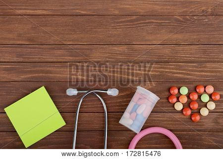 Stethoscope with paper note and pills on wooden table