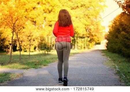 Young beautiful woman running in autumn park