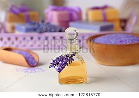Glass bottle of lavender essential oil and body care products on background