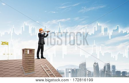 Young businessman in suit and safety hardhat on roof edge. Mixed media.