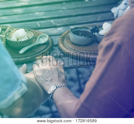 Couple holding hands and having sweet dessert