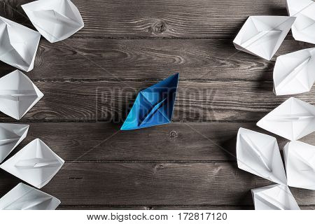 Set of origami boats on wooden table, one blue among all white.