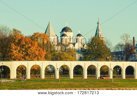 Veliky Novgorod Russia. Architecture autumn landscape - arcade of Yaroslav Courtyard ancient St Nicholas cathedral and people walking along in Veliky Novgorod Russia. Vintage tones applied