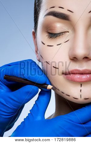 Beautiful girl with dark eyebrows at studio background, doctor's hand making marks on patient's face, portrait, perforation lines on face, closed eyes.