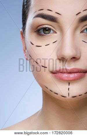 Portrait of girl with dark hair looking at camera at gray studio background, perforation lines on face.