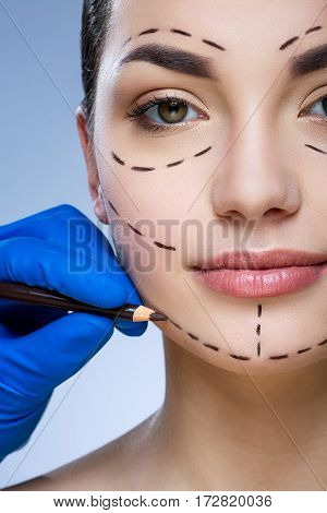 Perfect girl with dark eyebrows at studio background, doctor's hand making marks on patient's face, portrait, perforation lines on face.
