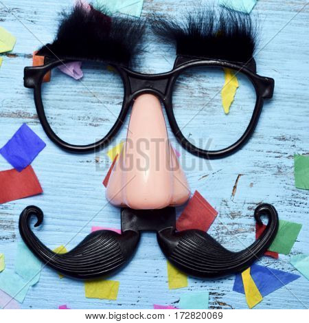 closeup of a pair of fake black glasses with eyebrows, a nose and a mustache forming the face of a man on a blue rustic wooden surface full of confetti