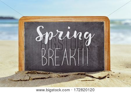 closeup of a wooden-framed chalkboard with the text spring break written in it, on the sand of a lonely beach