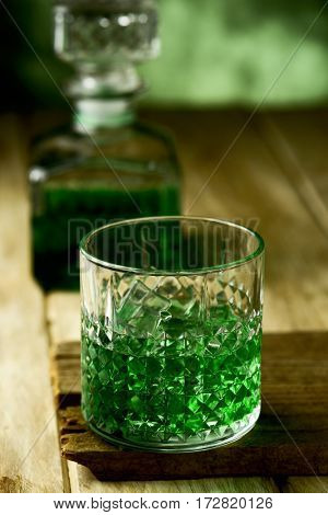 closeup of a glass with dyed green whiskey on a wooden rustic surface and a liquor bottle with dyed green in the background
