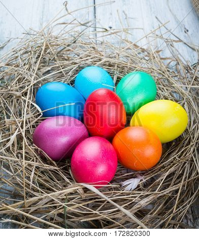 Group of colorful easter hen eggs in hay on sackcloth background. Easter eggs in straw nest