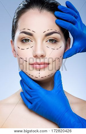 Nice girl with dark eyebrows at studio background, doctor's hands showing on patient's face, portrait, perforation lines on face.