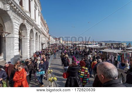 Venice, Italy - February 19 2017: Large crowd at Venice Carnival. People walking on the waterfront of Venice ready to enter the main area of celebrations for the Venice 2017 Carnival.