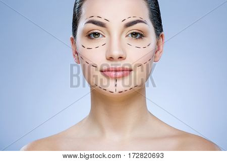 Cute girl with dark hair looking at camera at gray studio background, perforation lines on face, portrait, close up.