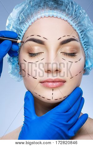 Portrait of girl with dark eyebrows wearing blue medical hat at studio background, doctor's hand making perforation lines on patient's face.