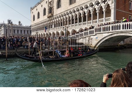 Venice, Italy - February 19 2017: A gondola with tourists under a bridge. A gondola with tourists wearing masks passes in front of Doges Palace heading to the Bridge Of Sighs.