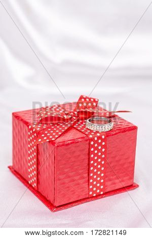 Red Gift Box With Red Bow And Diamond Ring Over White Satin