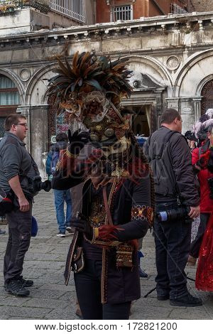 Venice, Italy - February 19 2017: Carnival mask and costume pose. Masked person in traditional costume poses at a Venetian square during the Venice 2017 Carnival.