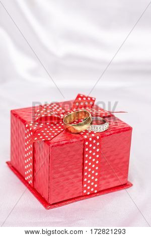 Red Gift Box With Bow And Wedding Rings Over White Satin