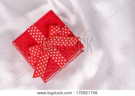 Flat Lay Red Gift Box With Bow Over White Satin