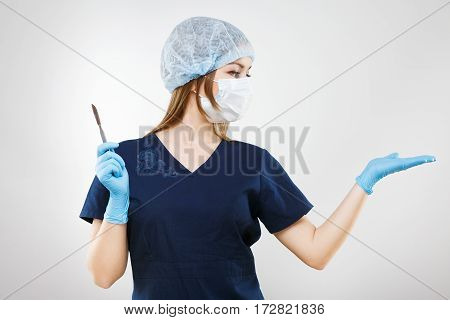 Nice nurse with brown hair and nude make up wearing blue medical uniform and gloves at gray background and holding a scalpel, pointing right.