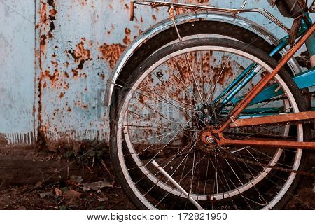 Two wheels off the bike next to the rusty garage