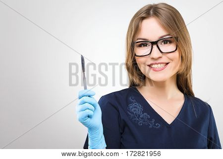 Beautiful nurse with brown hair and nude make up wearing blue medical uniform, glasses and gloves at gray background and holding a scalpel, smiling.