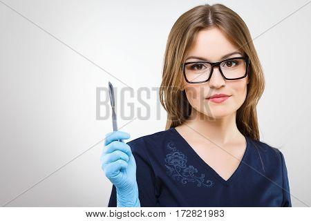 Attractive nurse with brown hair and nude make up wearing blue medical uniform, glasses and gloves at gray background and holding a scalpel.