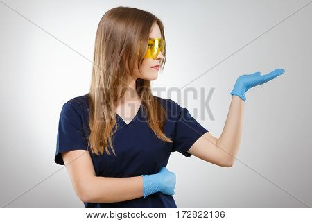 Pretty nurse with brown hair and nude make up wearing blue medical uniform, yellow glasses and gloves at gray background and pointing right, portrait.