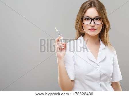 Beautiful nurse with brown hair and nude make up wearing white medical robe, glasses at gray background and posing with syringe, copy space.