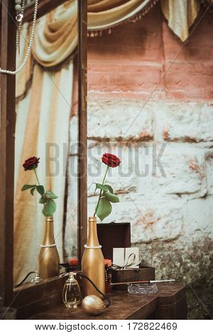 rose in a bottle and perfume, mouthpiece, ashtray on the dressing table