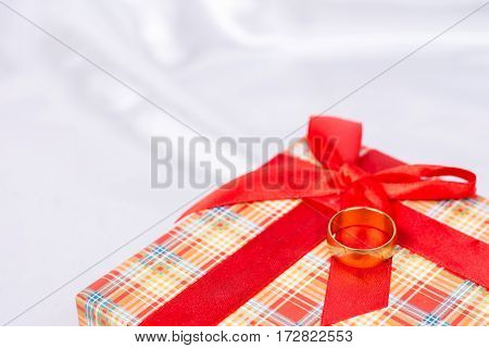 Gift Box With Wedding Ring On It Over White Satin