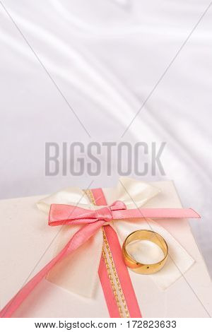 White Gift Box With Red Bow And Golden Wedding Ring