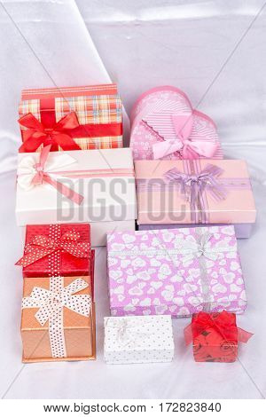Pile Of Gift Boxes With Bows Over White Satin