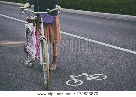 Young woman with bicycle standing on road near sign