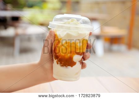 Female hand holding plastic cup of delicious cool dessert, closeup