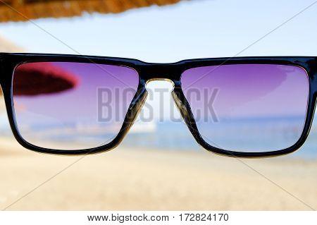 Black sunglasses at beach background, sea and umbrellas, copy space, close up.